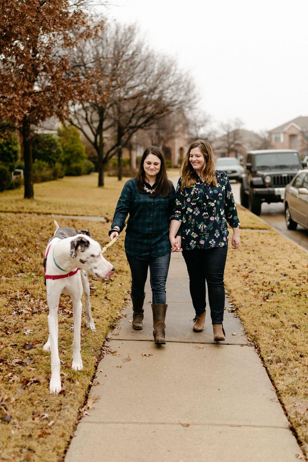 Married LGBTQ Couple walks their great dane