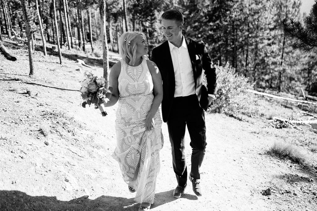 Bride and groom walk down a hiking trail in breckenridge