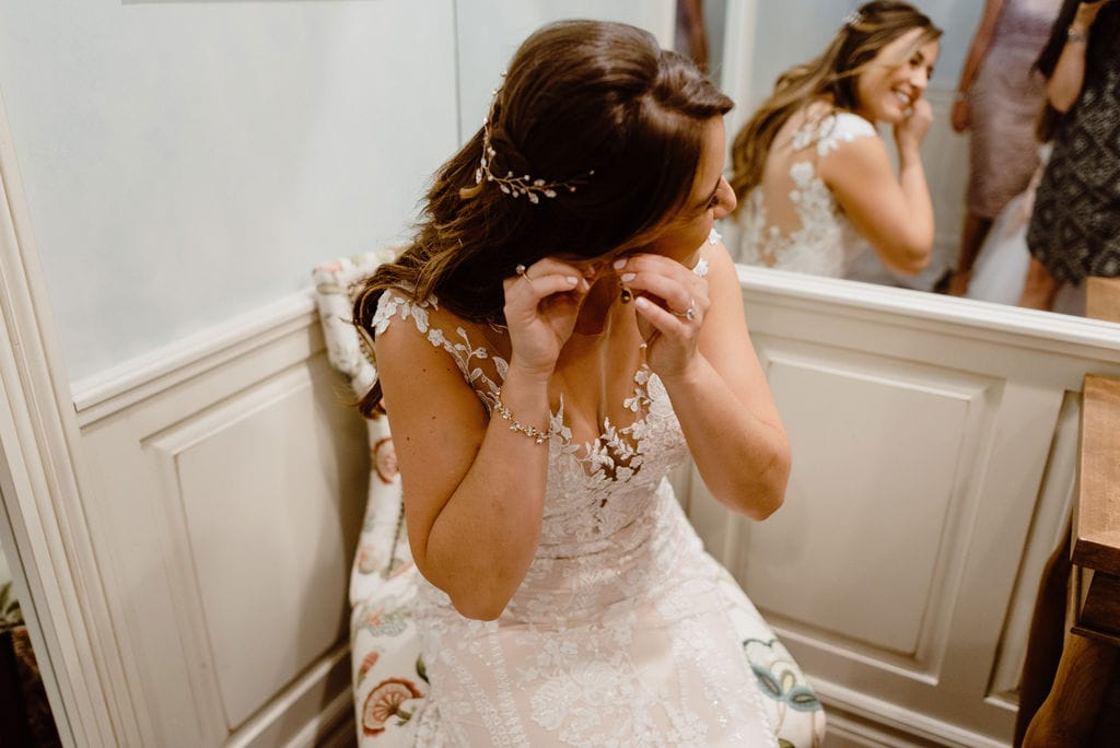 Bride putting on earings at Cheyenne Mountain Country Club