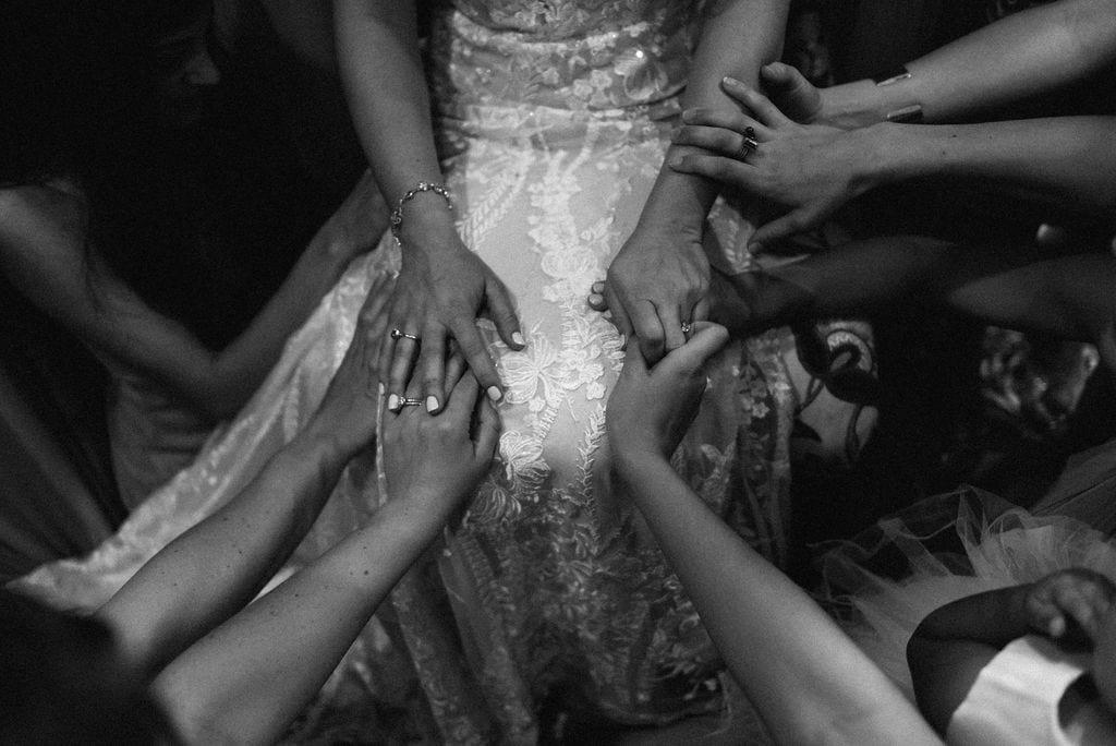 Hands on bride for prayer