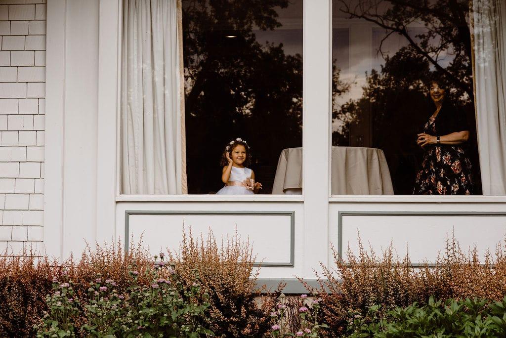 Girl peeking out window of wedding reception