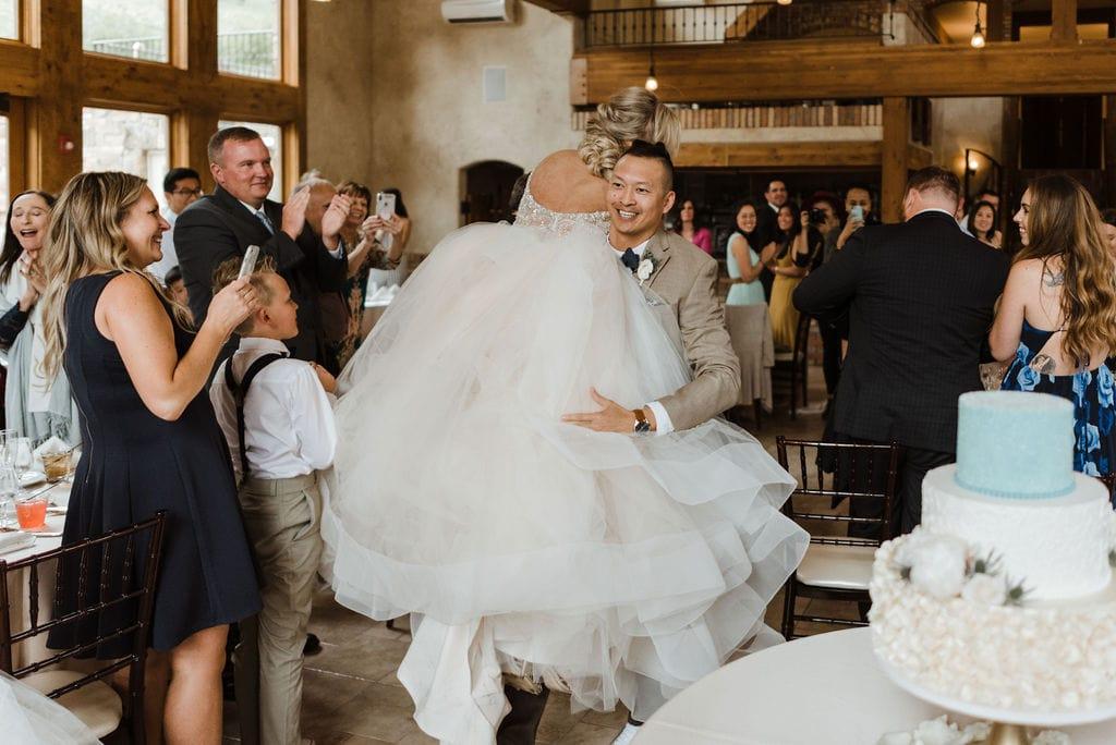 Groom carrying his bride through reception