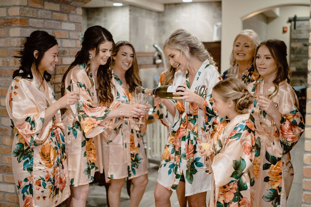 Bride with her Bridal Party Drinking Champagne While Getting Ready