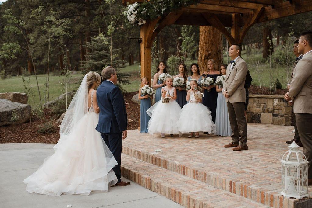Bride walking down aisle with her dad At Della Terra in Estes Park, Colorado