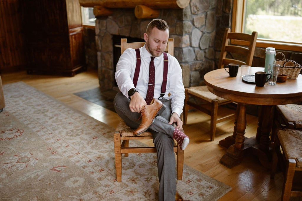 groom getting ready at cabin in colorado