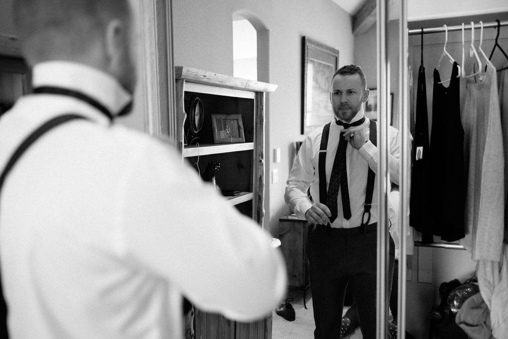 groom getting ready at rental cabin in colorado