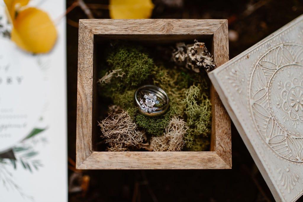 Wedding rings in moss inside ring box. Fall wedding decor.