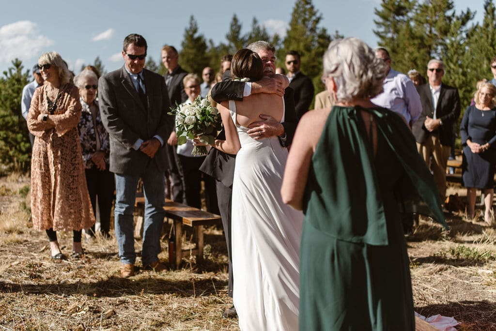 bride hugging father at their windy point campground wedding ceremony