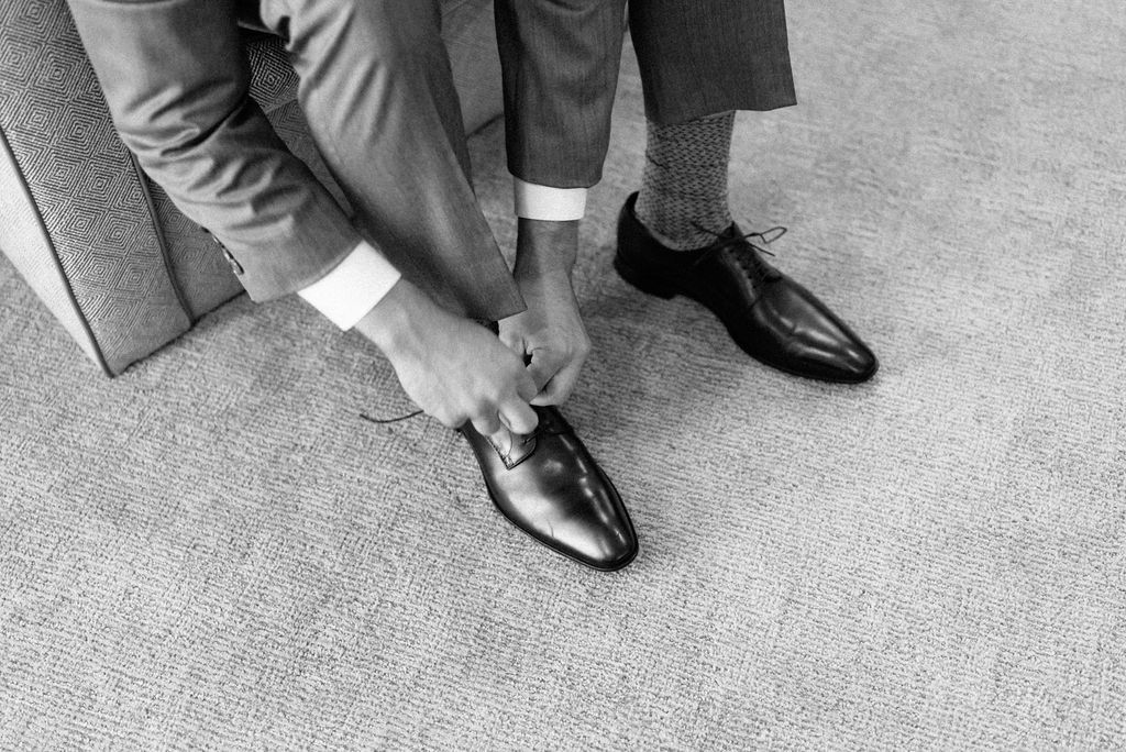 Groom putting on shoes at The Little Nell Hotel in Aspen Colorado
