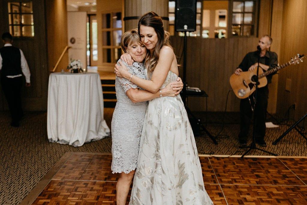Bride and her mom share an emotional hug together at her wedding