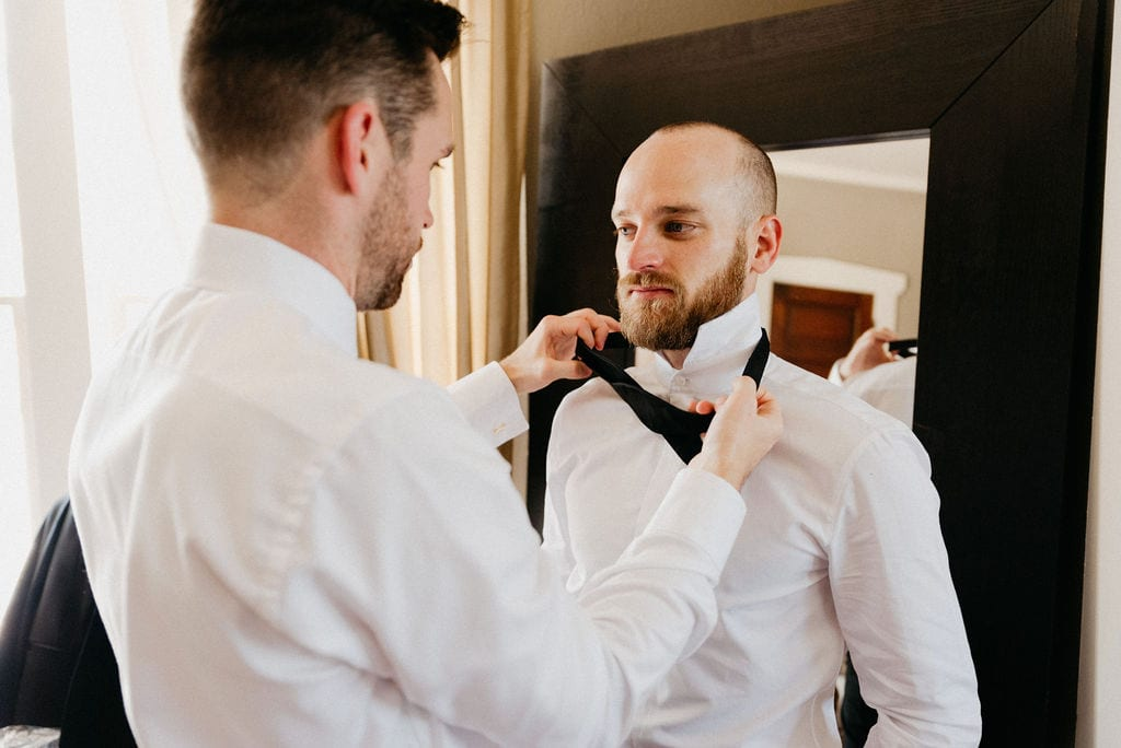 Groom puts on his tie with the help of his friend