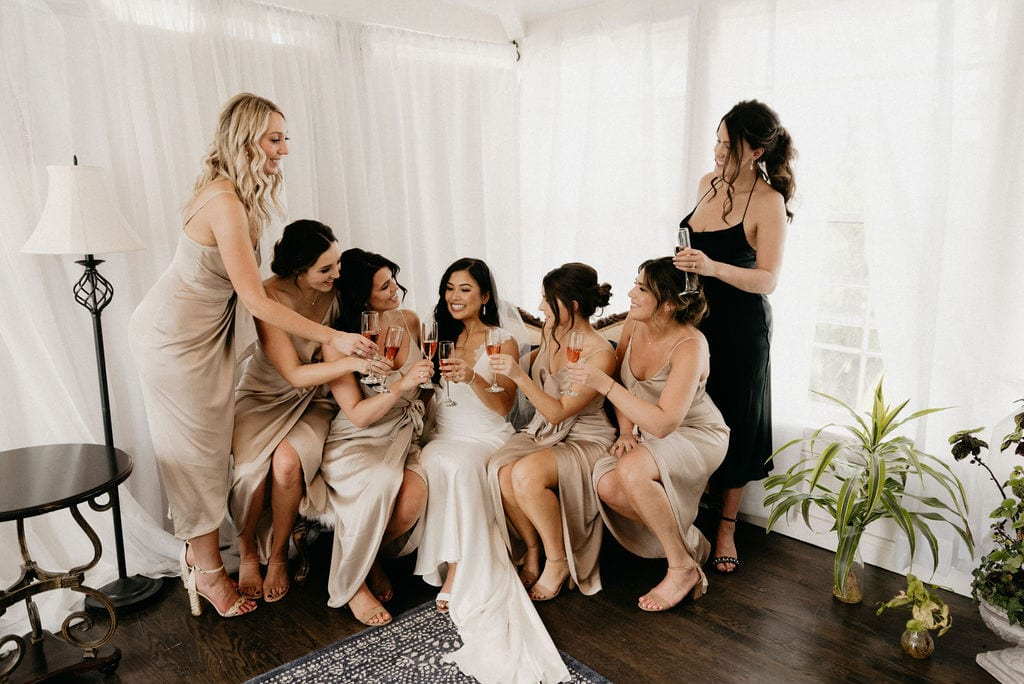 Bride and her bridesmaids cheers to the day