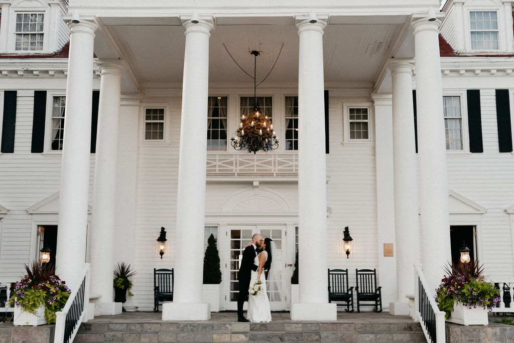 Bride and Groom Kissing at The Manor House on the porch