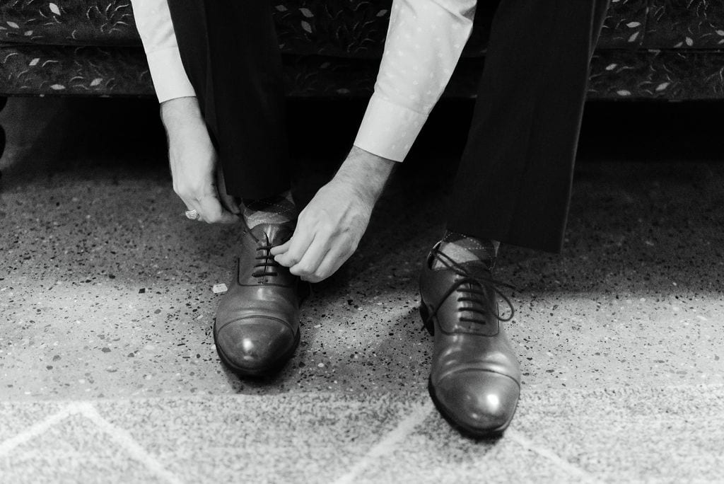 Groom tying his shoes in dallas