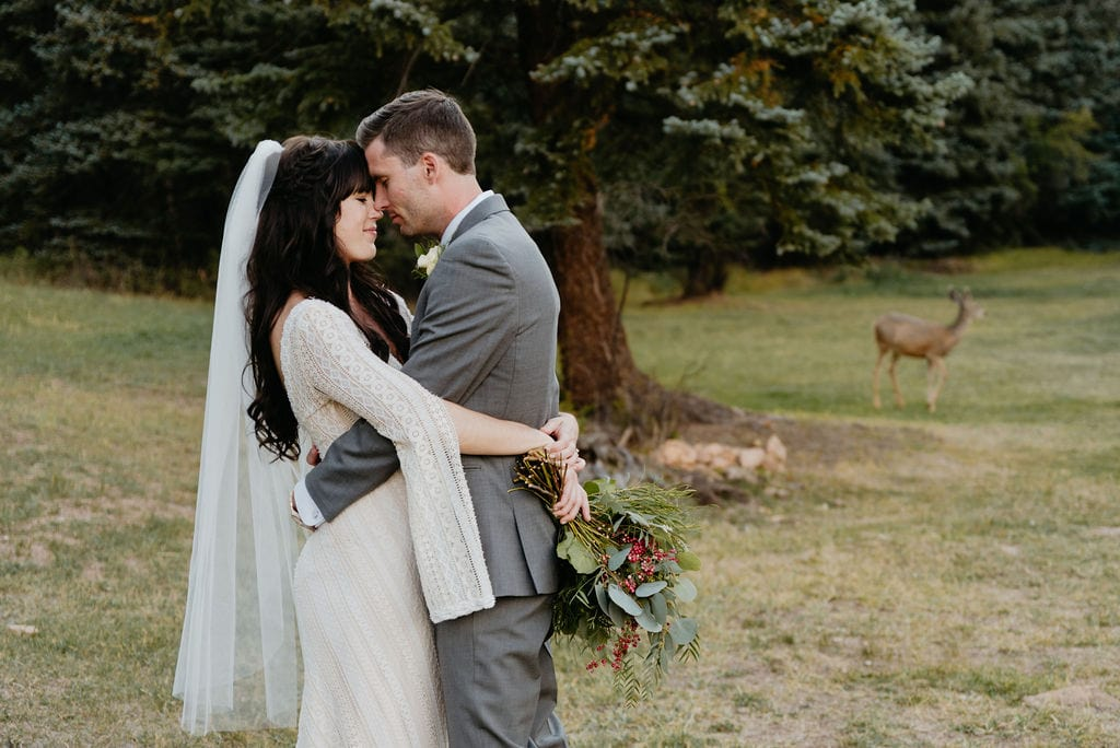 Bride and groom at mountain view ranch Deer in Background