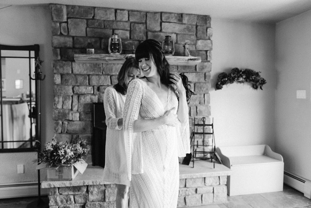 mom helping bride get into her dress at mountain view ranch