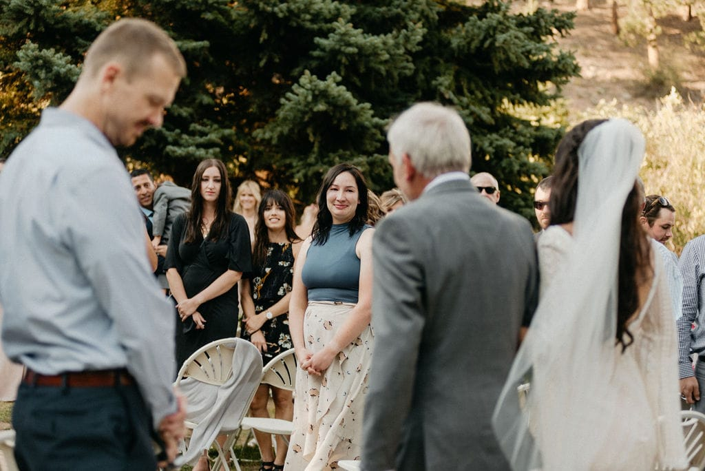 Guests looks at bride as she walks down the aisle