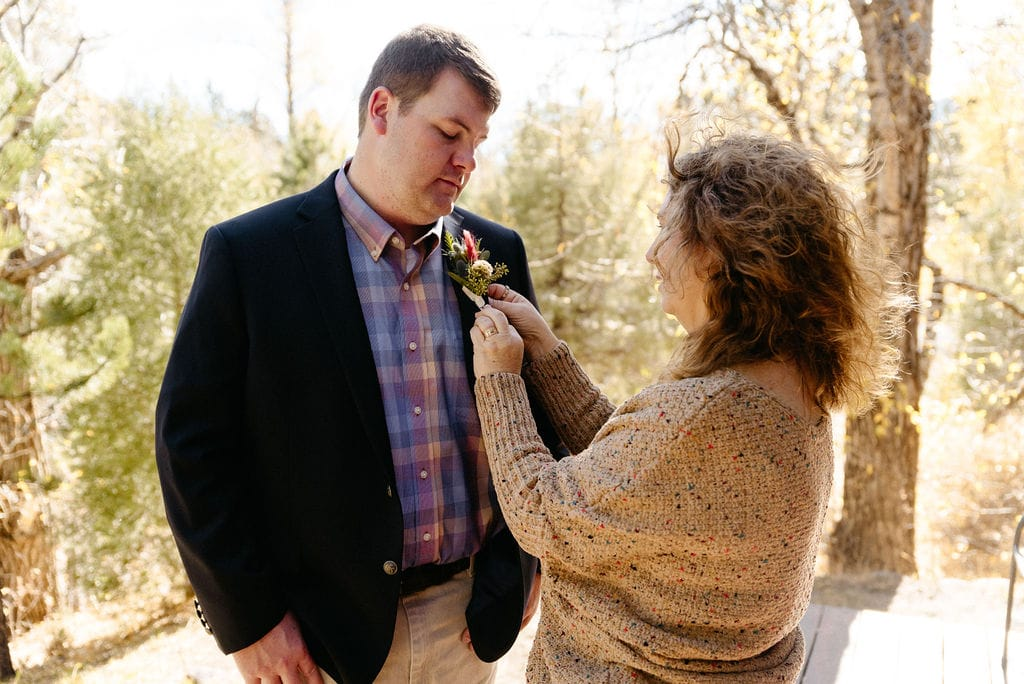 mom pins on boutonnière to the groom while getting ready for his estes park elopement