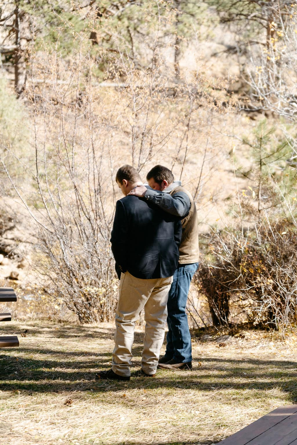 Groom and his father pray before his sprague lake elopement