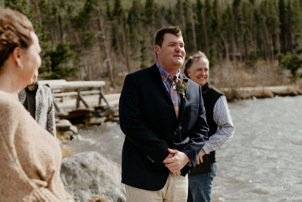 Groom sees bride walking to him at his sprague lake elopement