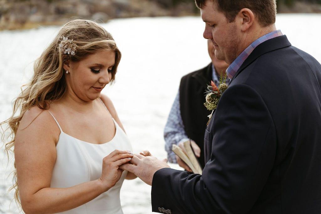 Bride and groom exchange rings at their sprague lake elopement