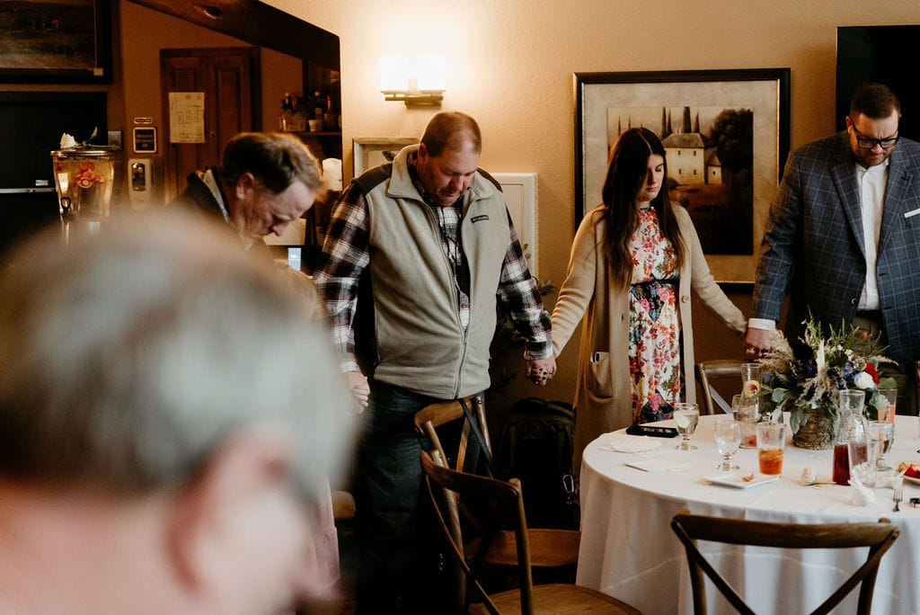 Bride and grooms family prays together before dinner at their estes park elopement