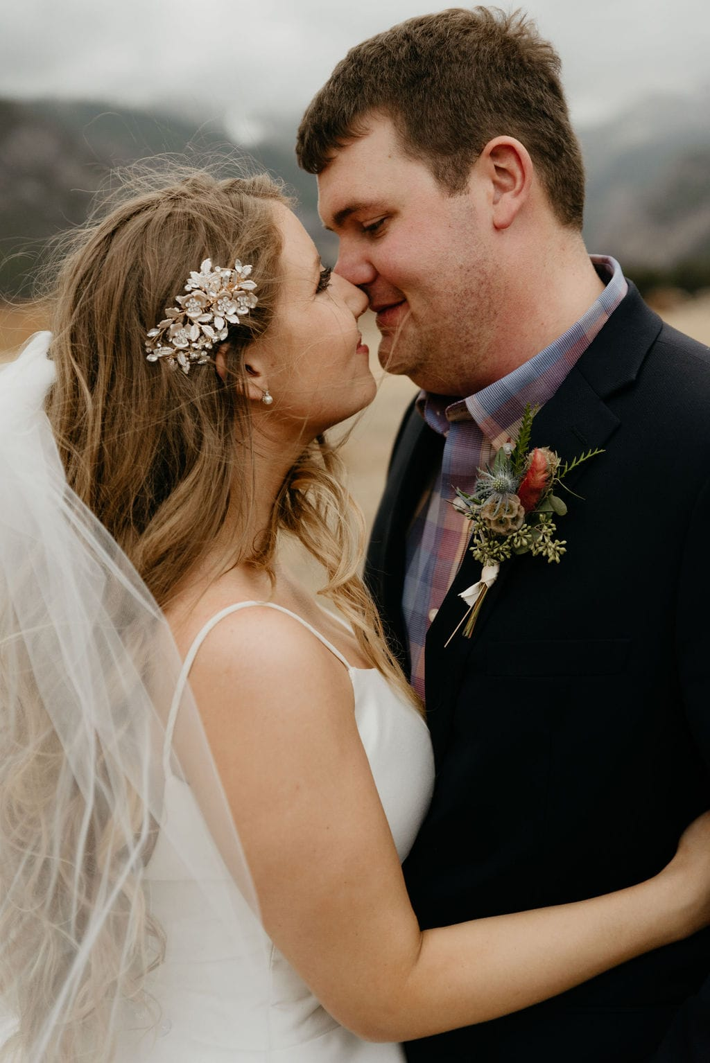 Close up portrait of bride and groom during high winds in estes park