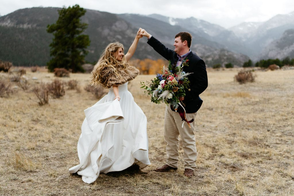 Bride and groom dance amongst mountains in rocky mountain national park