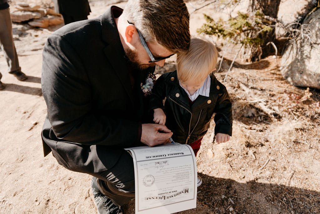 Bride and groom sign their marriage license at their hermit park elopement