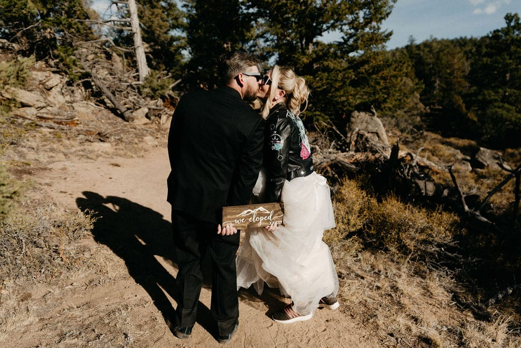 """Bride and groom holds """"we eloped"""" sign at their wedding ceremony spot in hermit park"""