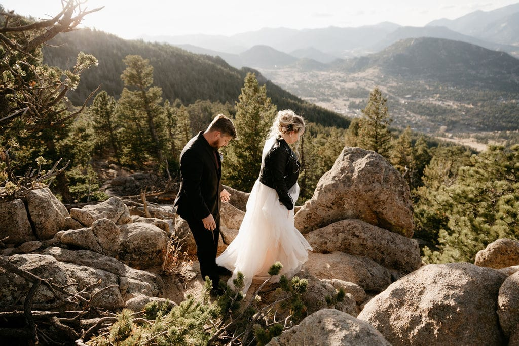 Bride and groom look down on the town of estes park from Kruger Rock Trail