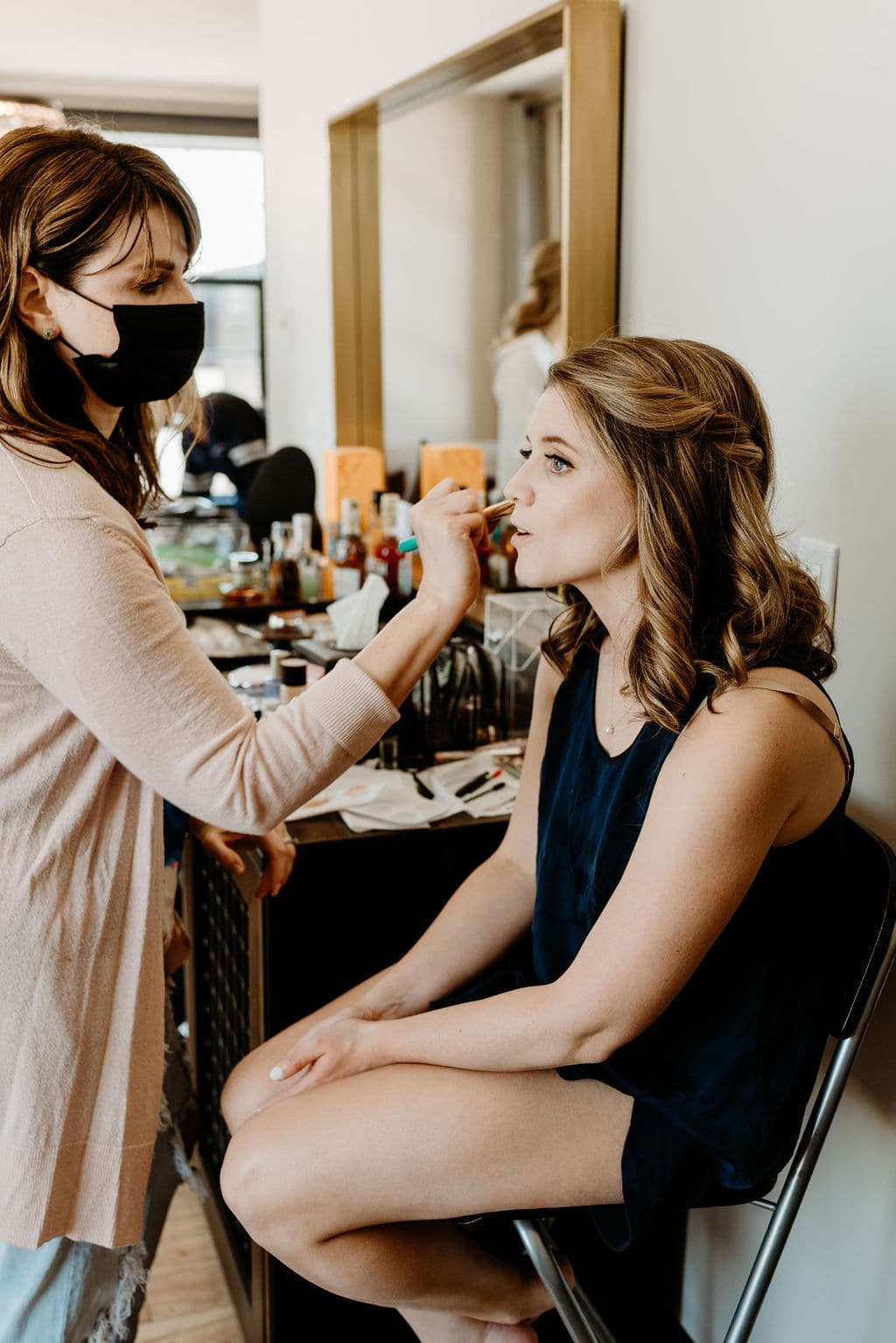 Bride getting makeup done at the ramble hotel before her Boulder colorado Elopement