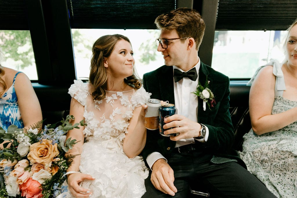 Couple cheers on a party bus on the way to their Boulder Colorado Elopement