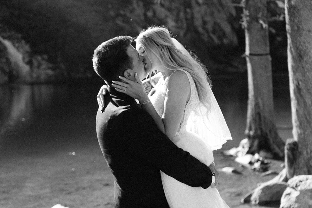 Lakeside romantic bride and groom kiss