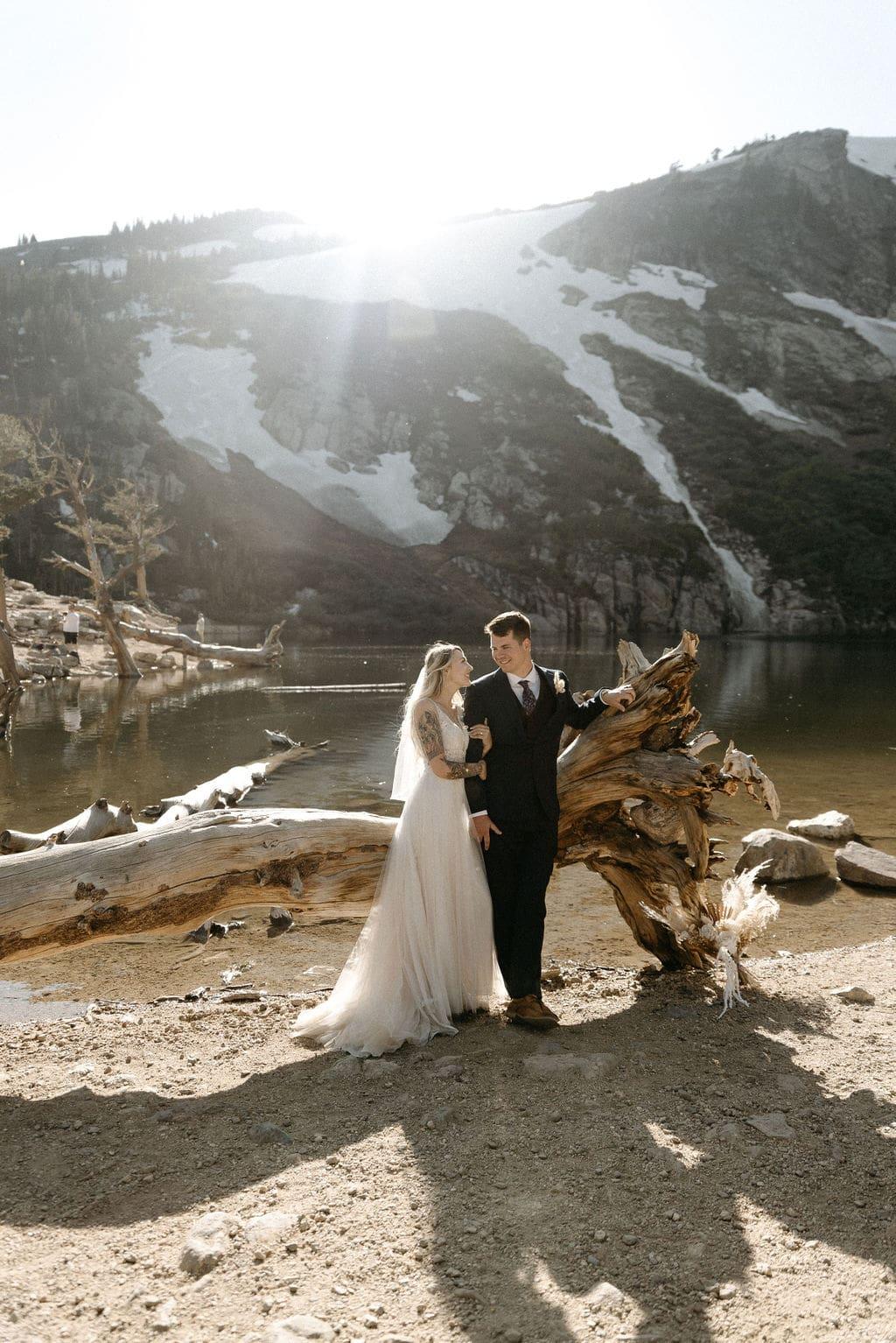 Bride and groom next to dead tree at st marys glacier in Colorado
