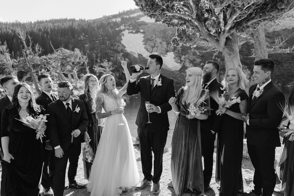 Popping champagne after wedding at st marys glacier