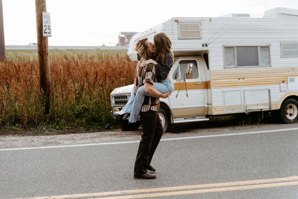 Girl running and jumping into her fiances arms for a romantic kiss during their 70s inspired denver engagement session