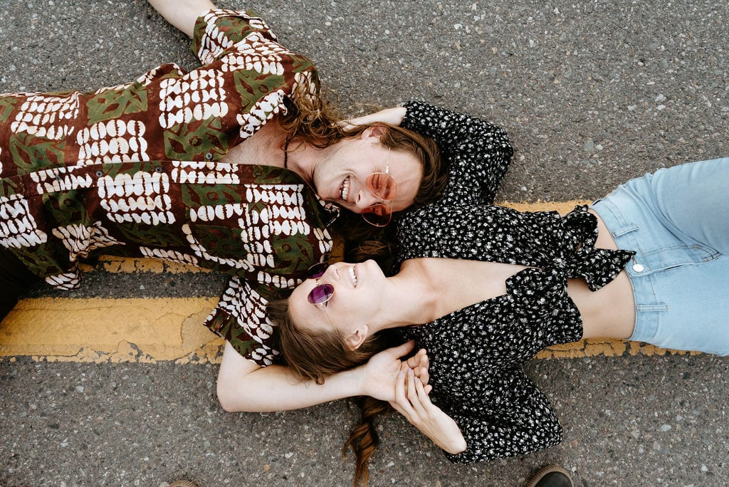70s fashion inspired engagement session. Couple lays down in the middle of the road