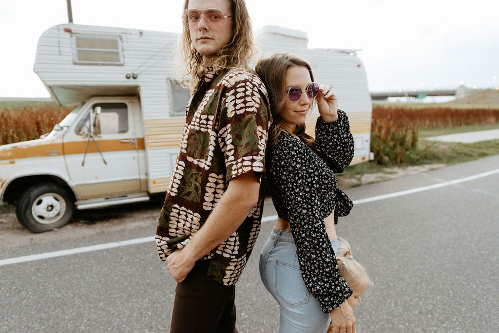 Couple with their daughter at their engagement photo session thats 70s inspired in denver colorado