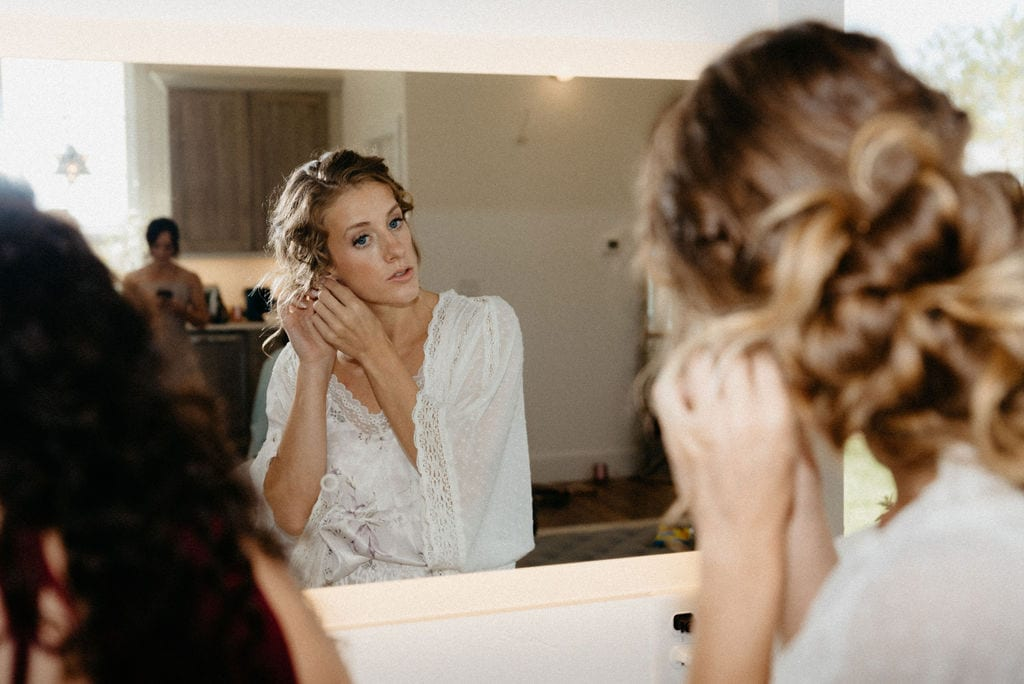 Bride puts her earings on at bonnie blues before her wedding