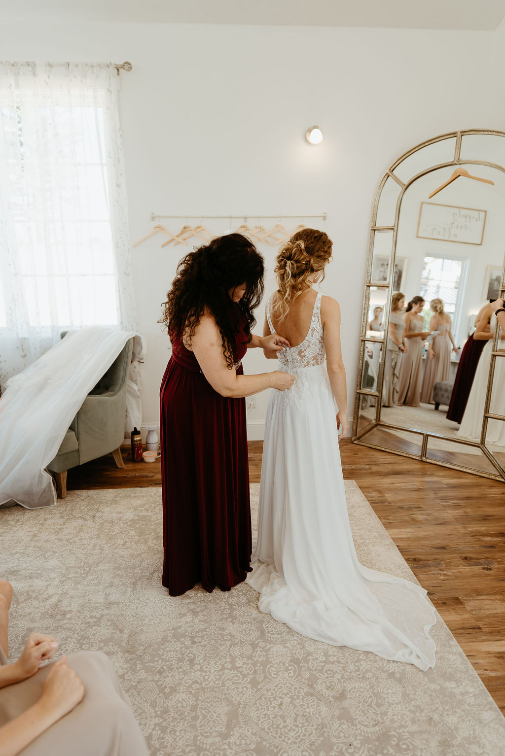 Mom helps bride button up her dress at bonnie blues event venue