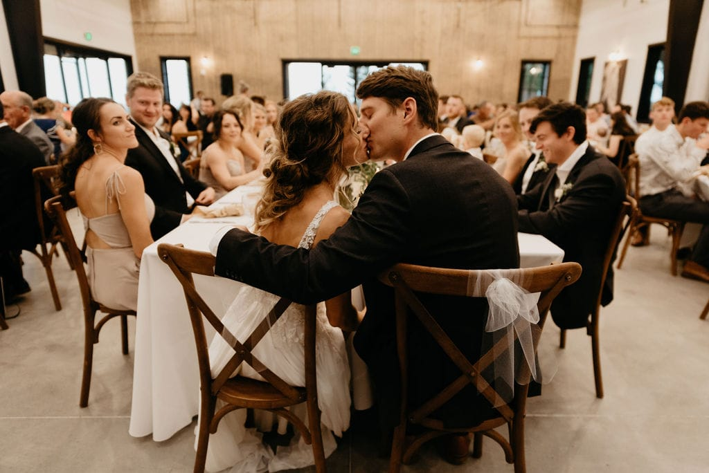 Bride and Groom Kiss at their wedding reception during the toasts